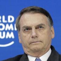 Gros plan du visage d'un homme avec en arrière-plan une murale sur laquelle on peut lire : World Economic Forum (Forum économique mondial).