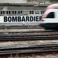 Un train suisse passe devant une publicité de Bombardier placardée sur un mur d'une gare de Berne en Suisse.