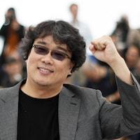 Un homme vêtu d'un veston et portant des lunettes fumées lève le poing.