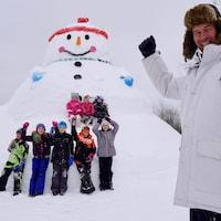 Un grand-père pose devant un bonhomme de neige.