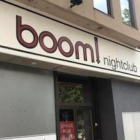 """La façade de la boîte de nuit Boom! avec une affiche dans la porte comportant l'inscription """"espace à louer"""" en anglais."""