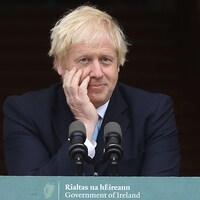 Boris Johnson place sa main droite sur son visage devant un lutrin.