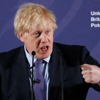 Boris Johnson parle dans des micros sur une scène.