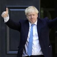 Boris Johnson, les deux pouces en l'air en signe de victoire.