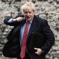 Boris Johnson traversant une rue pour se rendre au bureau du parti conservateur à Londres.