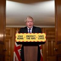 Boris Johnson se tient derrière un lutrin sur lequel on peut lire : « Restez à la maison, protégez le NHS [réseau de la santé], sauvez des vies. »