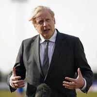 Boris Johnson répond aux questions des médias sur un terrain de soccer.