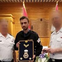 Un jeune homme en uniforme, accompagné de deux officiers, tient une enseigne militaire.