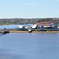 Une passerelle mène à une petite île où se dressent des maisonnettes d'allure ancienne et une salle de spectacle.