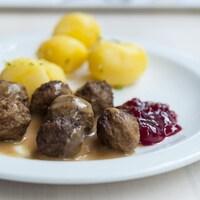 Des boulettes de viande servies dans une assiette accompagnées de pommes de terre, de sauce brune et de sauce aux canneberges, décorées d'un petit drapeau de la Suède.