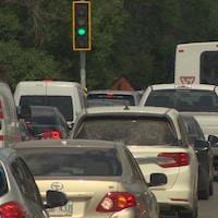 Circulation sur le boulevard à l'heure de pointe : une file de voitures et un autobus, vus de l'arrière.