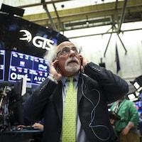 Un courtier lève les yeux vers des tableaux à la Bourse de New York.
