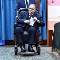 Le dirigeant algérien Abdelaziz Bouteflika assis sur une chaise roulante dans un bureau de vote lors des dernières élections parlementaires de mai 2017. Le président sortant, qui vient d'avoir 82 ans, apparaît rarement en public depuis qu'il a subi un accident vasculaire cérébral en 2013.