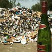 Une bouteille de verre devant une montagne de déchets recyclables.