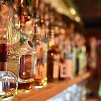 Des bouteilles d'alcools sur une tablette dans un bar.