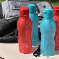Bouteilles d'eau en plastique à côté d'un sac d'école.