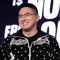 Bowen Yang, qui porte des lunettes, sourit.