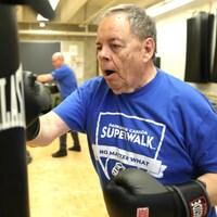 Gros plan sur un homme qui s'entraîne, gants de boxe aux mains.
