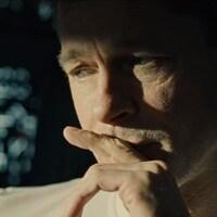 Un homme dans une station spatiale regarde au loin d'un air soucieux.