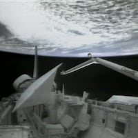 Vue du bras canadien dans l'espace attaché à la navette Columbia avec la Terre en arrière-plan.