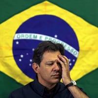 Le candidat de la gauche à la présidentielle brésilienne, Fernando Haddad, une main au visage devant un drapeau du Brésil.