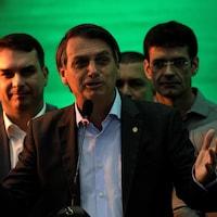 Un homme entouré de collaborateurs lors d'un rassemblement politique.
