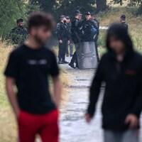 Des jeunes marchent sur un chemin de terre tandis que des policiers les regardent au loin.