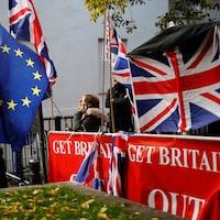 Des manifestants tiennent des drapeaux de l'Union européenne et du Royaume-Uni, devant une affiche rouge où est écrit « Get Britain Out ».