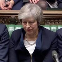 Theresa May, l'air défait, est assise au Parlement.