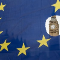 Un drapeau de l'Union européenne avec l'une des étoiles symboliquement découpées devant les chambres du Parlement.