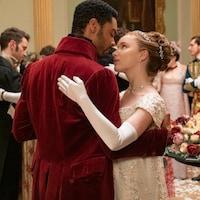 Un homme et une femme dansent en costume d'époque en se regardant dans les yeux.