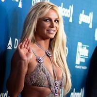 La chanteuse salue la caméra de la main lors d'un événement médiatique.