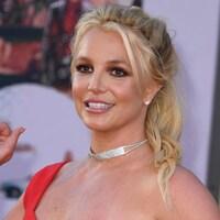 Britney Spears porte une robe rouge et un collier.