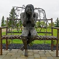 Sculpture de métal représentant une femme à la tête baissée assise sur un banc.