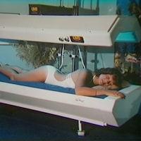 Femme en maillot de bain allongée sur un lit de bronzage