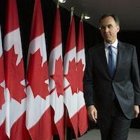 Bill Morneau debout devant plusieurs drapeaux canadiens.