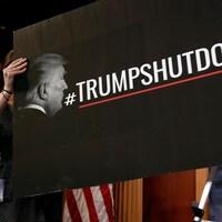 Un employé du parti démocrate accroche une pancarte blâmant le président Trump pour la paralysie budgétaire. On peut y lire le mot-clic #TrumpShutDown.