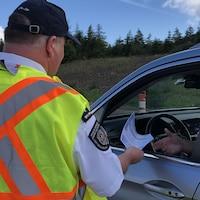 Un agent provincial remet un formulaire à un automobiliste.