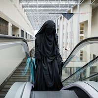 Une femme portant le niqab monte dans un escalier mécanique