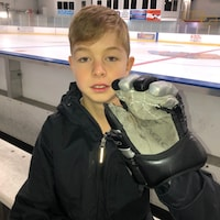 Carter Burton devant une patinoire montre son gant.