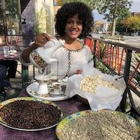 Une femme assise à la terrasse devant un homme qui parle au téléphone. Jebena à la main, elle verse le café dans des petites tasses rangées sur un plateau à côté de grains de café et de maïs soufflé.