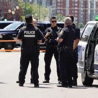 Une demi-douzaine de policiers réunis autour d'une voiture de patrouille.