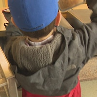 Un garçon chauffe son repas au micro-ondes.