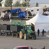 Une bâche, une tente et des personnes debout près d'une piste de course.