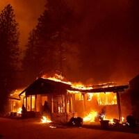 Une maison brûle dans un décor teinté de rouge et enfumé.