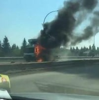Un camion en feu sur la route, une fumée épaisse s'en échappe.