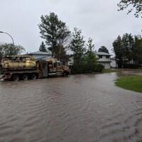Un camion-pompe circule dans une rue inondée d'un quartier résidentiel.