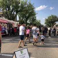 Des passants circulent et font la file devant des camions-restaurants.
