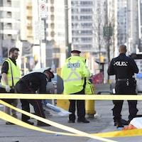 Des policiers torontois recueillent des objets près du corps d'une des victimes.