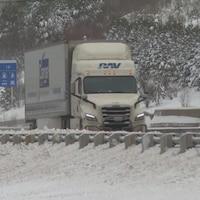 Un camion sur une route enneigée.